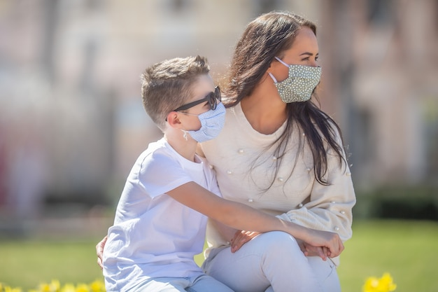 Matka i syn z maskami na twarzach patrzą w prawo w słoneczny dzień w parku.