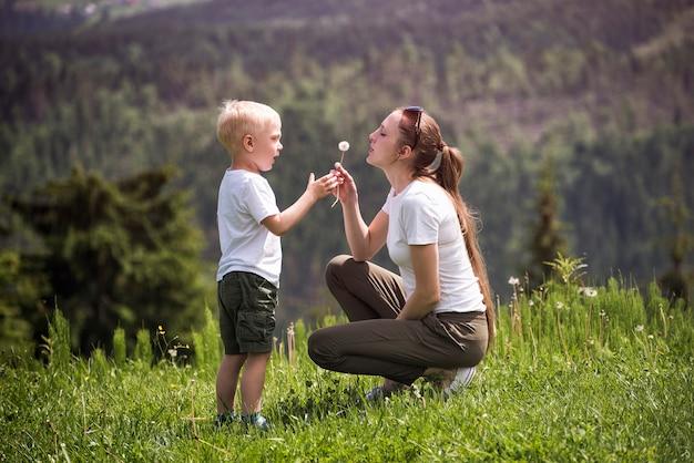 Matka i synek dmuchają mniszka lekarskiego. macierzyństwo i przyjaźń