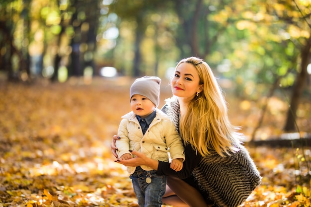 Matka i synek w parku lub lesie, na zewnątrz. przytulanie i wspólna zabawa w jesiennym parku