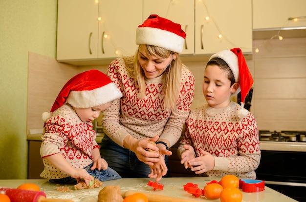 Matka i synowie przygotowują ciasto w kuchni. mama uczy swoich synów gotować, piec smaczne ciasteczka.