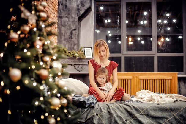 Matka i szczęśliwa córka w czerwonej piżamie wyglądają rodziny, siedząc razem na łóżku w pobliżu drzewa nowego roku w poddaszu wnętrza domu