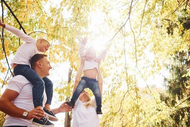 Matka i tata trzyma dzieci na ramionach iw rękach. wesoła młoda rodzina spaceruje razem w jesiennym parku.