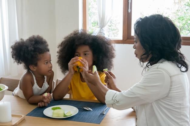 Matka je owoce z dziećmi w kuchni