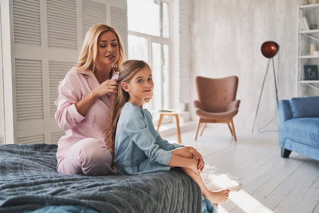 Matka jest najlepszą fryzjerką. piękna młoda matka szczotkująca włosy córki siedząc na łóżku w domu