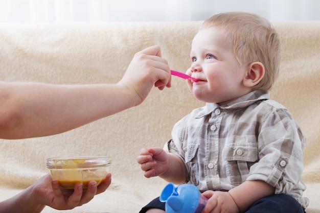Matka karmi małe dziecko przecierami owocowymi