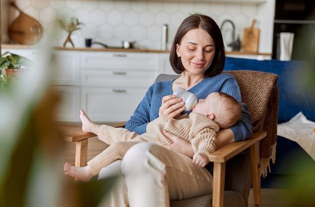Matka karmi noworodka z butelki z mlekiem. młoda szczęśliwa europejska kobieta i dziecko dziecko siedzi w drewnianym fotelu. wnętrze apartamentu typu studio. pojęcie macierzyństwa i opieki nad dzieckiem