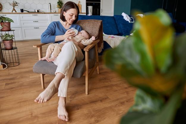 Matka karmi noworodka z butelki z mlekiem. młoda uśmiechnięta europejska kobieta i jej niemowlę siedzą w drewnianym fotelu. wnętrze apartamentu typu studio. pojęcie macierzyństwa i opieki nad dzieckiem