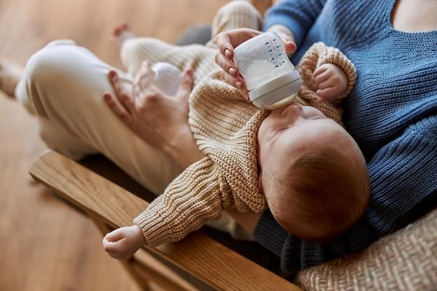 Matka karmi swoje nowo narodzone dziecko z butelki z mlekiem. kobieta i europejskie dziecko dziecko siedzi w drewnianym fotelu. wnętrze apartamentu typu studio. pojęcie macierzyństwa i opieki nad dzieckiem