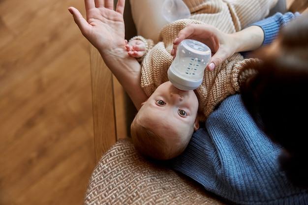 Matka karmi swoje nowo narodzone dziecko z butelki z mlekiem. kobieta i jej dziecko kaukaski niemowlę siedzi w drewnianym fotelu. wnętrze apartamentu typu studio. pojęcie macierzyństwa i opieki nad dzieckiem