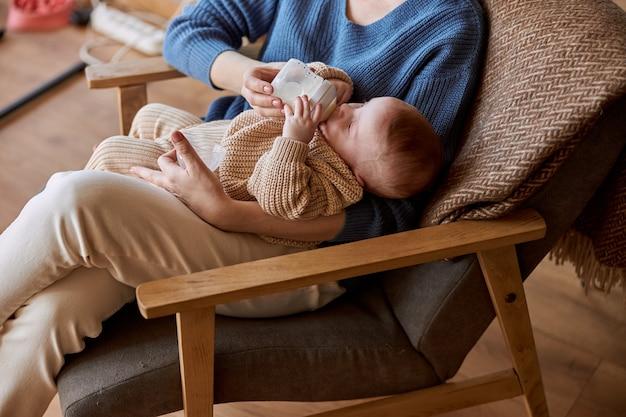 Matka karmi swoje nowo narodzone dziecko z butelki z mlekiem. kobieta i jej europejskie dziecko siedzi w drewnianym fotelu. wnętrze apartamentu typu studio. pojęcie macierzyństwa i opieki nad dzieckiem