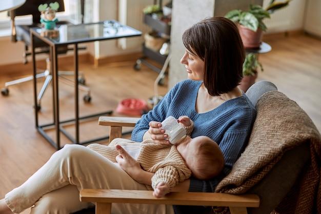 Matka karmi swoje nowo narodzone dziecko z butelki z mlekiem. młoda kobieta kaukaski i dziecko dziecko siedzi w drewnianym fotelu. wnętrze apartamentu typu studio. pojęcie macierzyństwa i opieki nad dzieckiem
