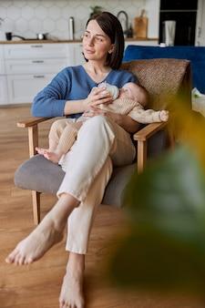 Matka karmi swoje nowo narodzone dziecko z butelki z mlekiem. młoda zamyślona europejka i małe dziecko siedzą w drewnianym fotelu. wnętrze apartamentu typu studio. pojęcie macierzyństwa i opieki nad dzieckiem