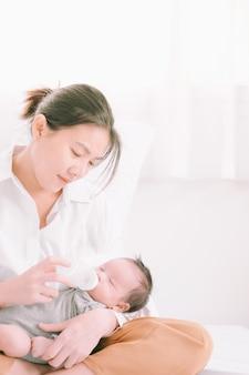 Matka karmiąca pokój swojego uroczego noworodka w domu. kobieta karmi noworodka zmodyfikowanym mlekiem z butelki