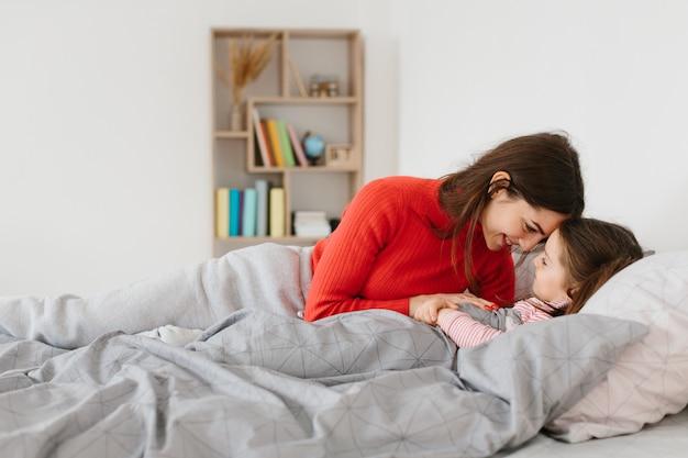 Matka kładzie małą córeczkę do snu.