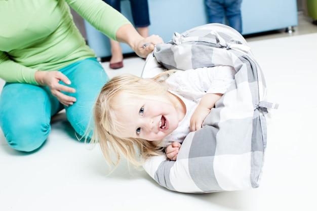 Matka kołysze córkę z poduszką na podłodze