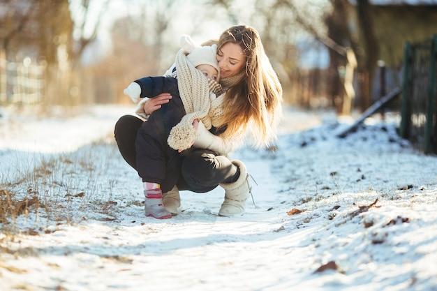 Matka kucki z jej małego chłopca w ramionach na zaśnieżonej ulicy