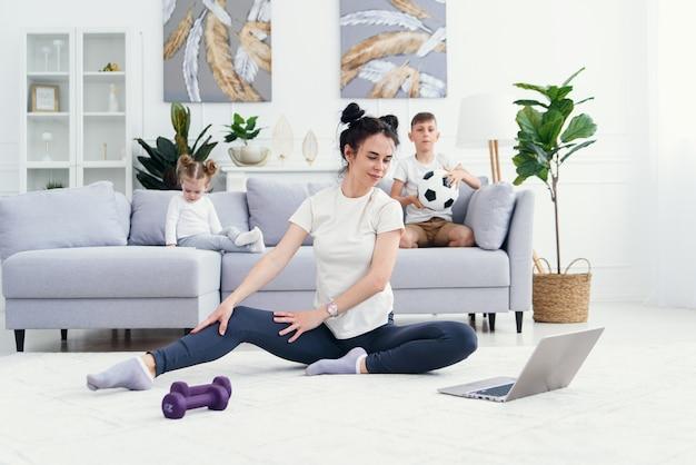 Matka medytuje z córką, podczas gdy aktywny, energiczny syn dziecko bawi się, mama pracuje i robi ćwiczenia jogi w domu dla odprężenia relaksując się z niegrzecznym małym dzieckiem. 4 k wideo zwolnione tempo