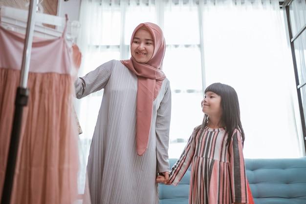 Matka muzułmanka wybierając sukienkę dla córki razem w sklepie odzieżowym. zakupy dla mamy i dziecka w butiku