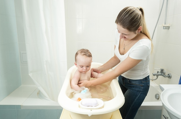 Matka myjąca swojego synka w wannie