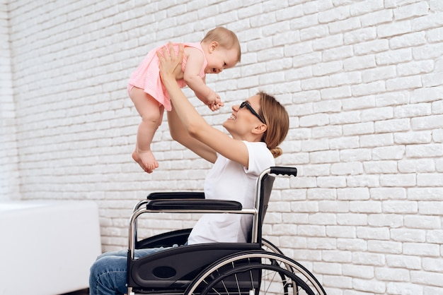 Matka na wózku inwalidzkim bawić się z nowonarodzonym dzieckiem.