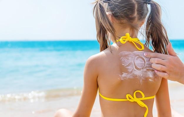 Matka nakłada krem przeciwsłoneczny na plecy córki na plaży