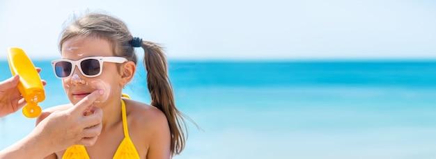 Matka nakłada krem przeciwsłoneczny na twarz córki na plaży