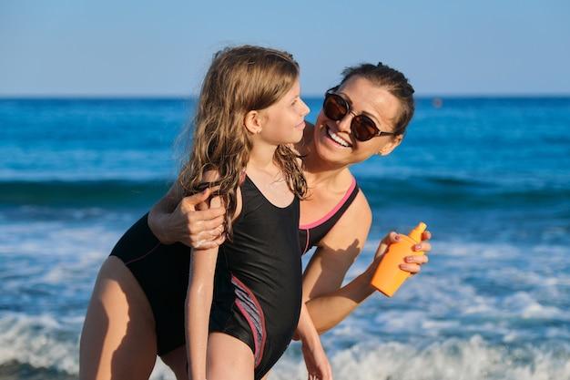 Matka nakłada krem z filtrem na córkę na plaży, odpoczywa rodzic i dziecko