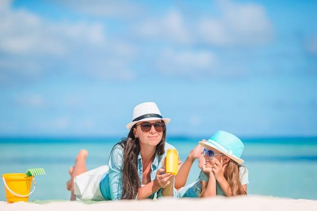 Matka nakłada krem z filtrem przeciwsłonecznym na małą córeczkę na plaży w gorący letni dzień