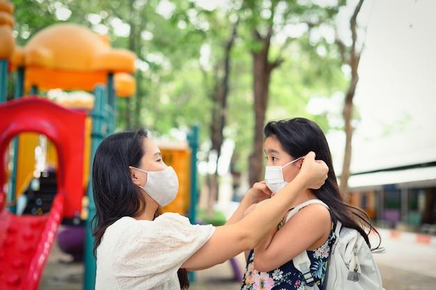 Matka nakłada maskę ochronną na twarz córki w celu ochrony przed epidemią koronawirusa w wiejskim parku, aby przygotować się do szkoły. powrót do koncepcji szkoły. maska medyczna zapobiegająca koronawirusowi.