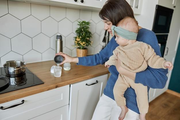 Matka nalewa wodę do butelki, aby przygotować mleko dla noworodka. młoda kobieta gospodarstwa dziecko dziecko. wnętrze kuchni w mieszkaniu. pojęcie macierzyństwa i opieki nad dzieckiem
