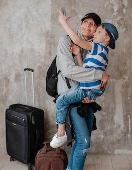 Matka niesie małego syna na walizce w poczekalni transportu.