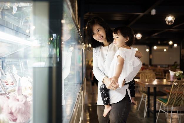 Matka niosąca córkę, patrząc na wystawę sklepu w restauracji