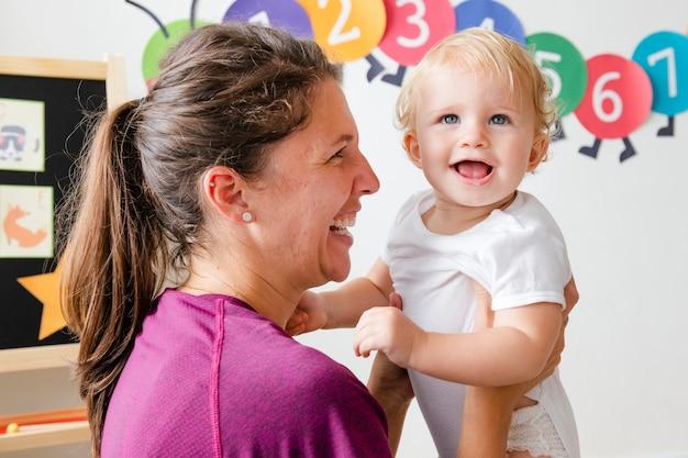 Matka niosąca i bawiąca się z dzieckiem