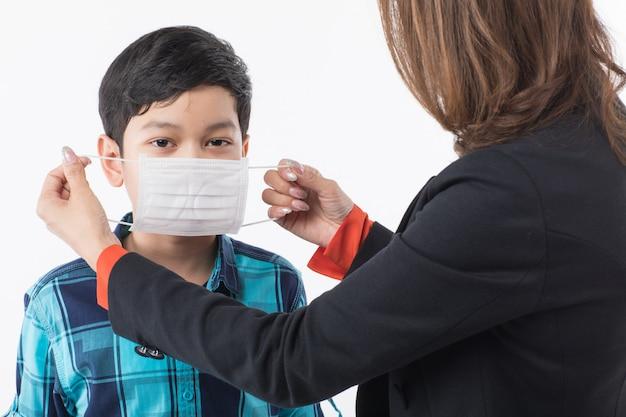 Matka nosi maskę chirurgiczną dla syna.