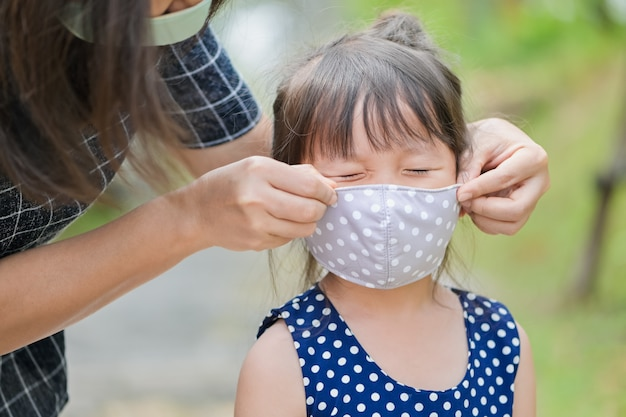 Matka nosi maskę ochronną dla małej dziewczynki, która chroni przed koronawirusem, gdy dziecko wychodzi z domu