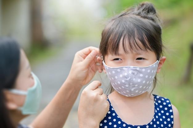 Matka nosi maskę z materiału dla małej dziewczynki, chroniąc przed chorobami lub zanieczyszczeniem powietrza