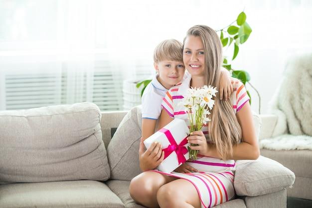 Matka obejmuje jej małe dziecko. szczęśliwa rodzina. mama i jej uroczy syn w domu.