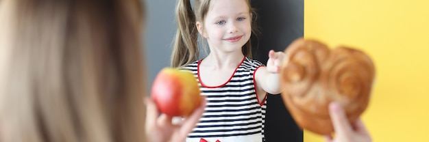 Matka oferująca małej dziewczynce bułkę lub czerwone jabłko