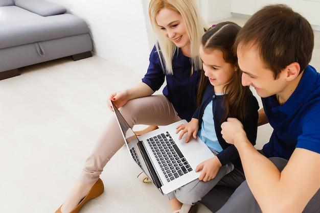 Matka, ojciec i córka studiują na laptopie. dystans społeczny i samoizolacja w kwarantannie