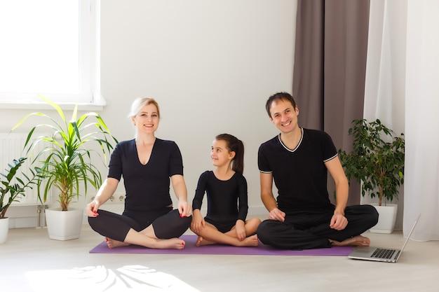 Matka, ojciec i córka uprawiają jogę