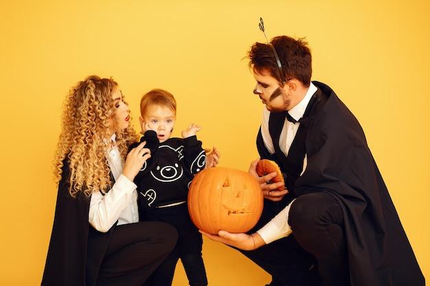 Matka, ojciec i dzieci w kostiumach i makijażu. ludzie stojący na żółtym tle.