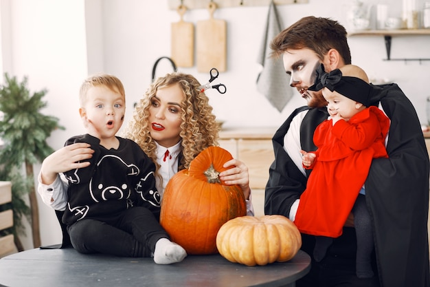 Matka, ojciec i dzieci w kostiumach i makijażu. rodzina przygotowuje się do świętowania halloween.