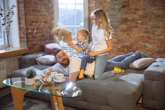 Matka, ojciec i syn w domu bawią się komfortem i przytulną koncepcją