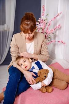 Matka opiekuje się dzieckiem wieczorem. młoda matka przytula swojego synka w łóżku. szczęśliwa matka i jej małe dziecko czytające bajkę na dobranoc w domu. mama i syn odpoczywają w łóżku w domu. śpij dobrze