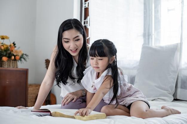 Matka opowiada córce historie na białym łóżku.