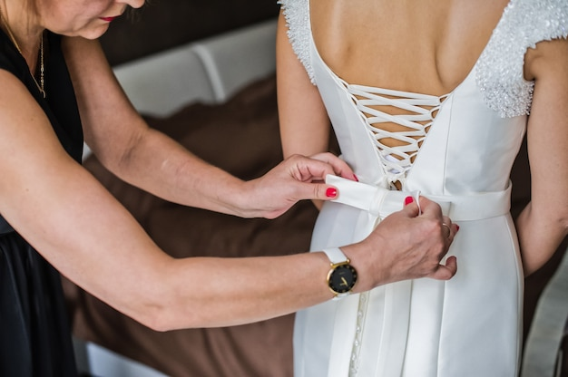 Matka panny młodej pomaga pannie młodej nosić sukienkę