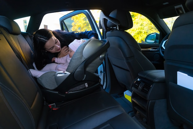 Matka patrząca na swoje dziecko w foteliku na tylnym siedzeniu samochodu z czarnym wnętrzem, sięgająca przez otwarte drzwi, ujęcie z boku z miejscem na kopię
