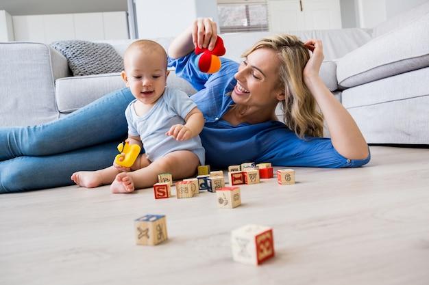 Matka patrzy na chłopca grając z zabawkami w salonie
