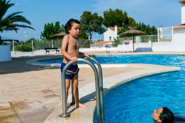 Matka patrzy na swojego syna z basenu, podczas gdy dziecko jest na zewnątrz przywiązane do mokrej drabiny