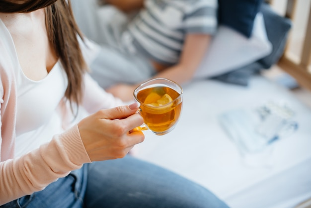 Matka podaje swojemu dziecku gorącą herbatę z cytryną podczas choroby i wirusa. medycyna i opieka.